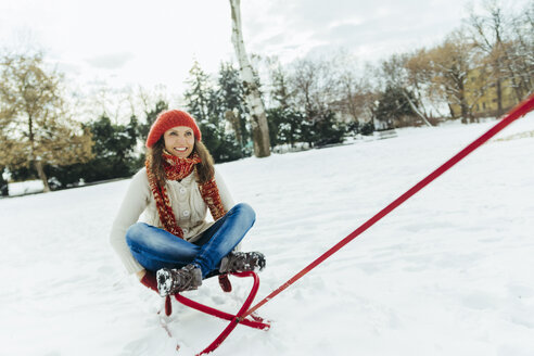 Smiling woman sitting on sledge - ZEDF00820