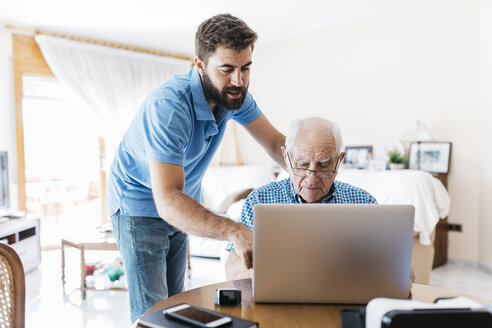 Adult grandson teaching his grandfather to use laptop - JRFF01414