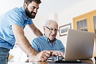Adult grandson teaching his grandfather to use laptop - JRFF01417