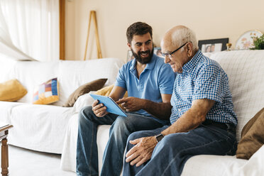 Adult grandson teaching his grandfather to use tablet - JRFF01426