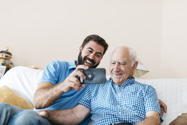Portrait of adult grandson and his grandfather taking selfie with smartphone at home - JRFF01429