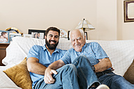 Portrait of adult grandson and his grandfather sitting on the couch at home tickling each other - JRFF01432