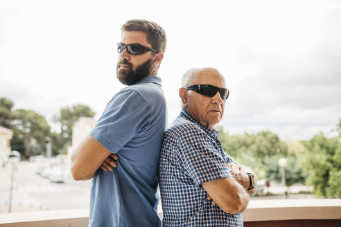 Portrait of adult grandson and his grandfather wearing sunglasses standing back to back on balcony - JRFF01438