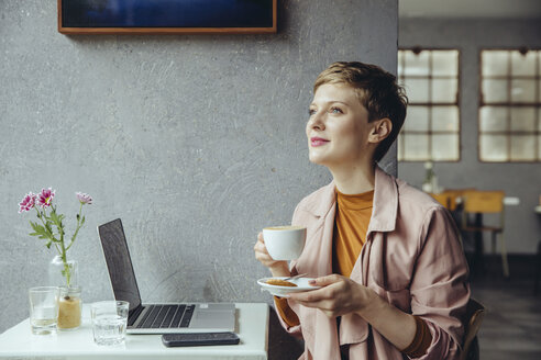 Woman with her laptop enjoying a cup of coffee in a cafe - MFF03825