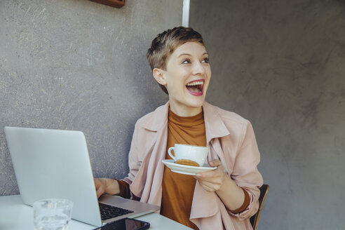 Surprised woman with her laptop enjoying a cup of coffee in a cafe - MFF03831