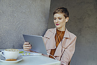 Woman with tablet and earbuds in a cafe - MFF03837