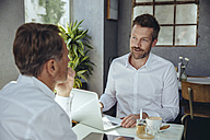 Two businessmen having a meeting in a cafe - MFF03843