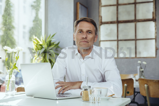 Portrait of businessman in cafe with laptop - MFF03858
