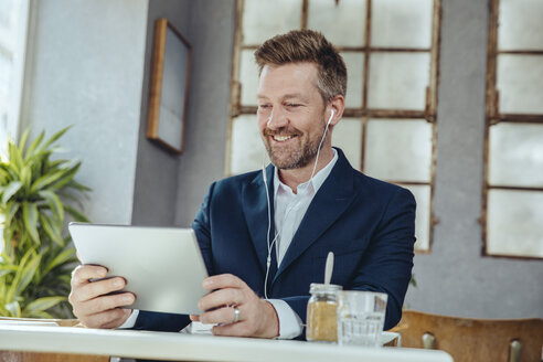 Smiling businessman with tablet and earbuds in a cafe - MFF03861