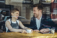 Waitress serving coffee to smiling customer in cafe - MFF03870