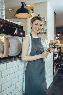 Portrait of smiling waitress holding menu in a cafe - MFF03873