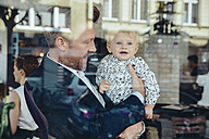 Businessman holding his baby boy in cafe - MFF03876
