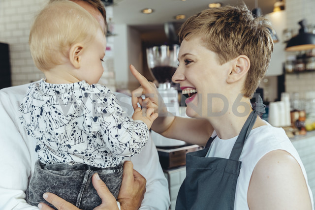 Waitress playing with baby of customer in cafe - MFF03879