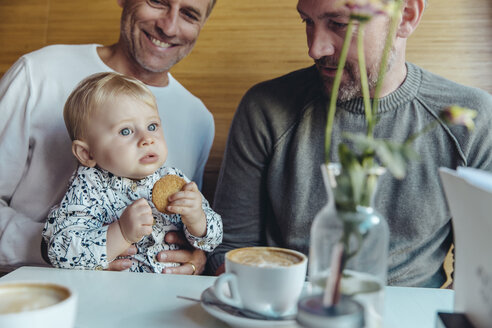 Gay couple looking at their baby in cafe - MFF03885