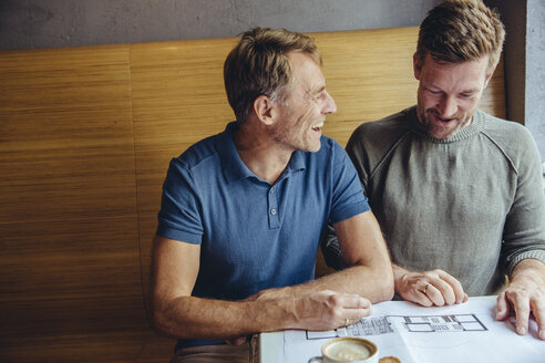 Happy gay couple looking at constructions plans for their home in cafe - MFF03894
