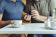 Close-up of gay couple with wedding ring in cafe - MFF03897