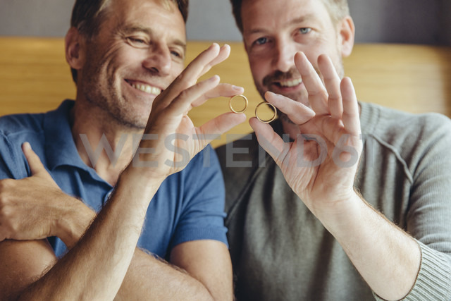 Happy gay couple holding up their wedding rings - MFF03900 - Mareen Fischinger/Westend61
