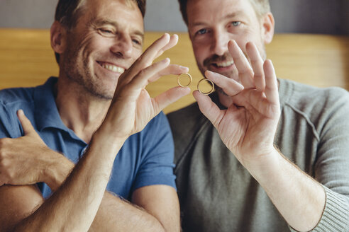 Happy gay couple holding up their wedding rings - MFF03900