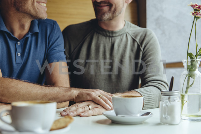 Gay couple putting their hands together with wedding rings in cafe - MFF03903