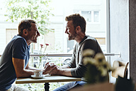 Gay couple holding hands in cafe while looking at one another - MFF03909