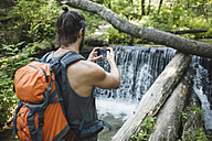 Young man taking a cell phone picture at a waterfall in forest - VPIF00030