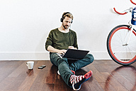 Man with headphones sitting on the floor at home using laptop - GIOF03161