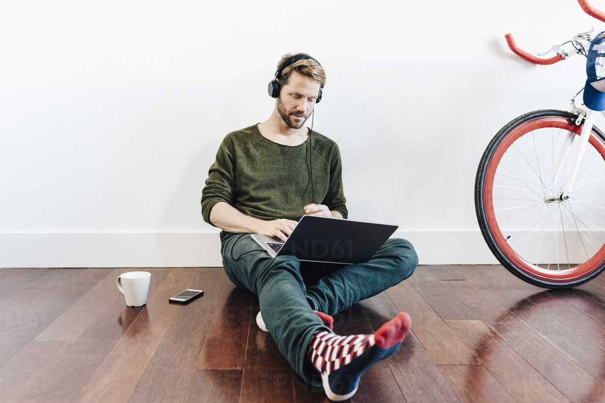 Man with headphones sitting on the floor at home using laptop - GIOF03161 - Giorgio Fochesato/Westend61