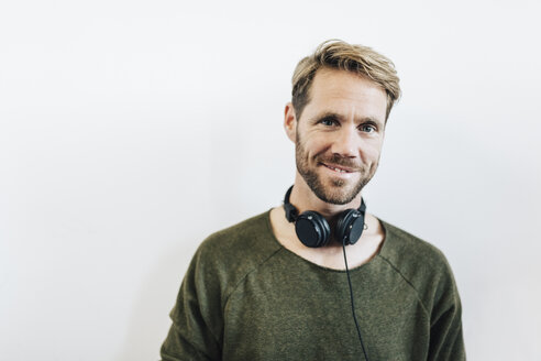 Portrait of smiling man with headphones against white background - GIOF03164