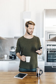 Portrait of man standing in kitchen looking at cell phone - GIOF03170