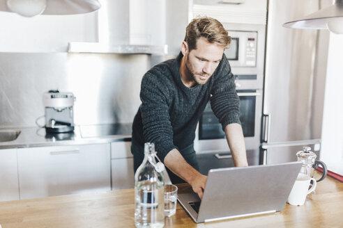 Portrait of man standing in kitchen using laptop - GIOF03176