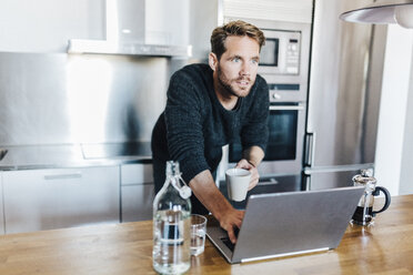 Portrait of starring man with coffee mug and laptop standing in kitchen - GIOF03179