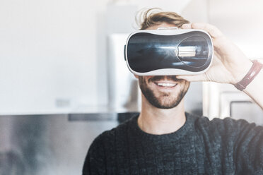 Smiling man wearing Virtual Reality Glasses - GIOF03185