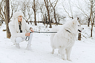 White dressed young woman with white dog in the snow watching something - ZEDF00825