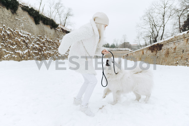 Young woman playing with her dog in the snow - ZEDF00828