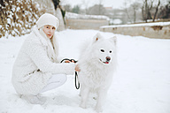 Portrait of white dressed young woman with white dog in the snow - ZEDF00831
