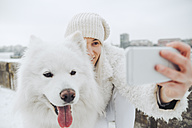 Serbia, Petrovaradin, white dressed woman taking selfie with white dog in winter - ZEDF00837