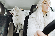 White dressed young woman driving car with white dog on the backseat - ZEDF00840