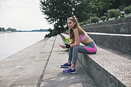Sporty woman having a break at the riverbank - MOMF00229