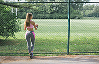 Rear view of young woman standing at fence - MOMF00232