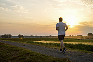 Man running in rural landscape at sunset - PUF00690