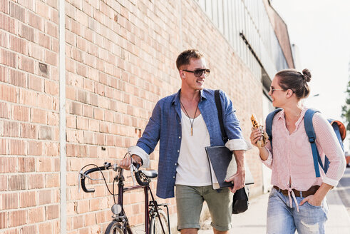 Young couple with bicycle walking and talking - UUF11516