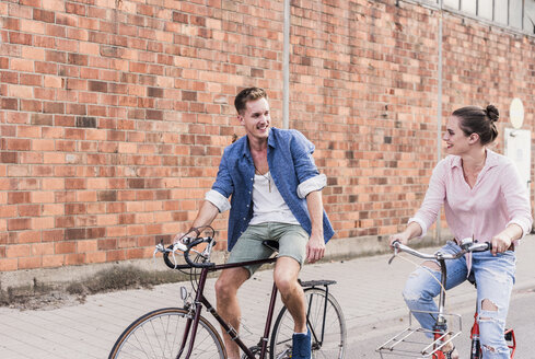 Young couple riding bicycle - UUF11525