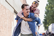Young man giving girlfriend piggyback ride - UUF11528