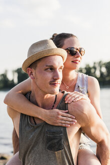 Young man giving girlfriend piggyback ride at the riverbank - UUF11534