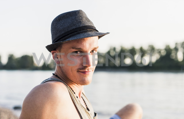 Portrait of young man wearing a hat at the riverbank - UUF11537