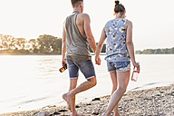 Young couple walking at the riverbank - UUF11543