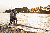 Happy young couple wading in river at sunset - UUF11546