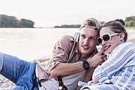 Young couple relaxing at the riverbank sharing headphones - UUF11549