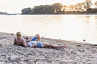 Young couple relaxing at the riverbank at sunset - UUF11552