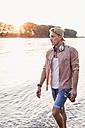 Young man walking at the riverbank at sunset - UUF11555